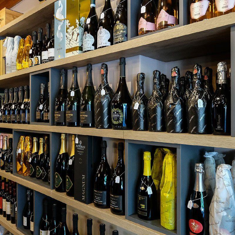 Vista dello scaffale lungo, pieno di bottiglie di pregiato vino